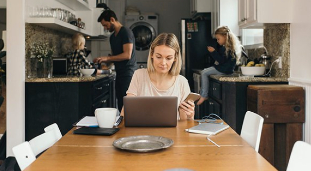 Woman working on laptop in kitchen