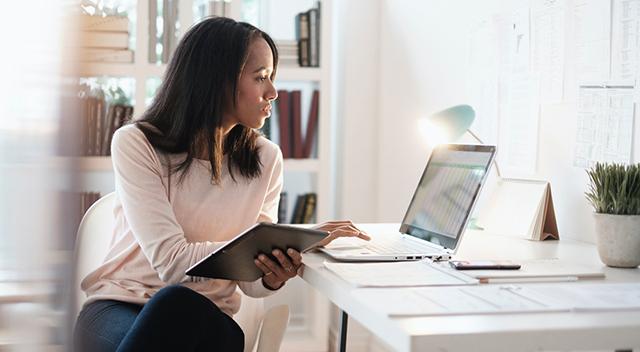 Una mujer con una camisa blanca mira una laptop con una revista en su otra mano