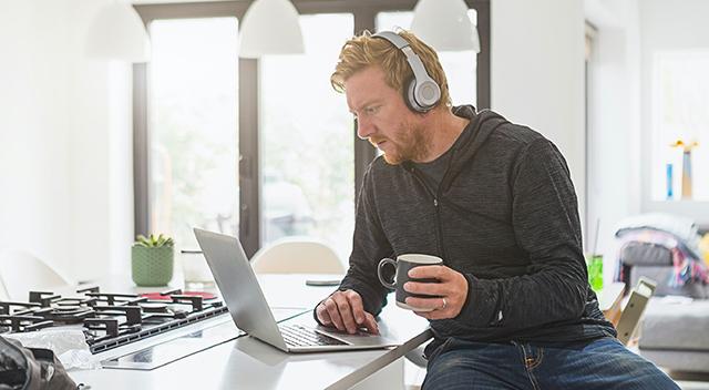 Un hombre sentado con auriculares sostiene una taza y tiene su otra mano sobre una laptop