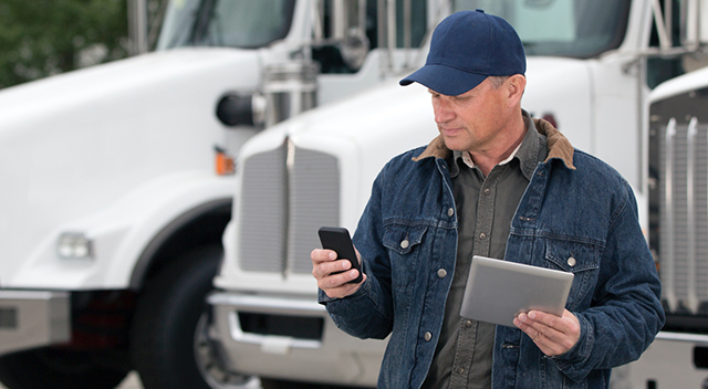 Man standing by trucks and looking at a mobile device