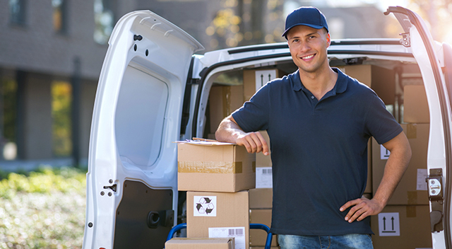 Smiling man standing at the back of a truck with his elbow propped on boxes