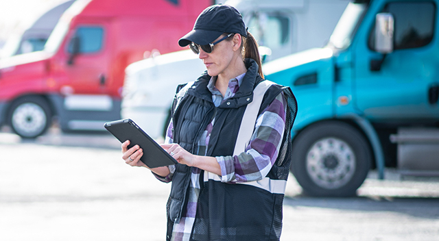 Woman standing by trucks looking at a tablet