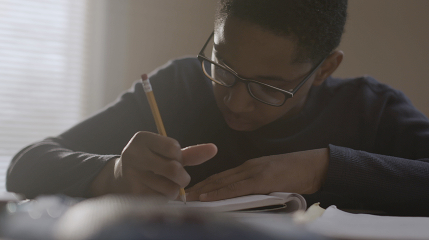 Student holding pencil, doing homework