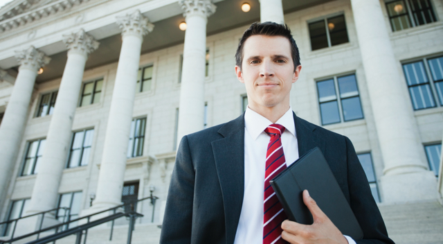 Man in jacket and red tie outside government building with pillars