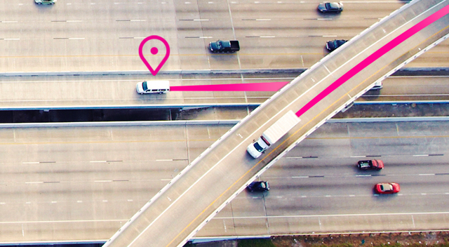 Overhead shot of cars and trucks driving on a highway followed by a magenta line