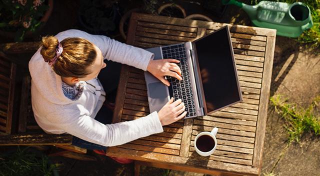 Toma aérea de una mujer vistiendo una sudadera gris con capucha, trabajando en exteriores en una laptop.