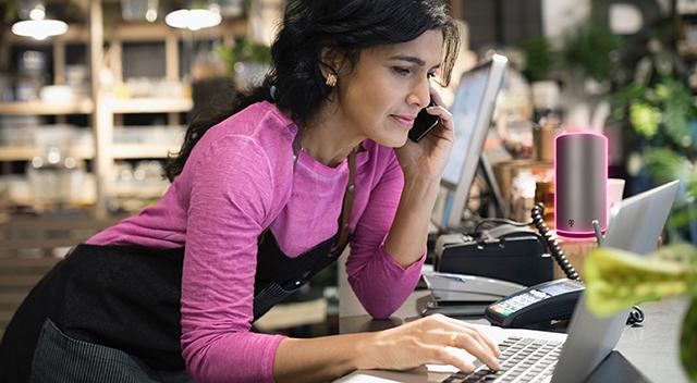 Mujer vestida con una camiseta magenta y un delantal oscuro apoyada sobre un escritorio mientras habla por teléfono.