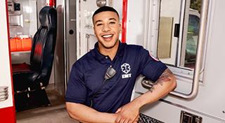 Técnico de servicios de emergencia sentado y sonriendo.