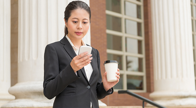 Woman in a blazer stands while holding a coffee cup and looking at her smartphone