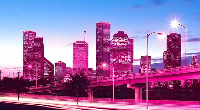 Cluster of city buildings at dusk with purple tint.