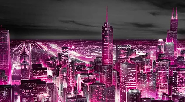 Big city at night lit up with a purple tint.