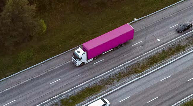 Magenta semi truck driving down a highway