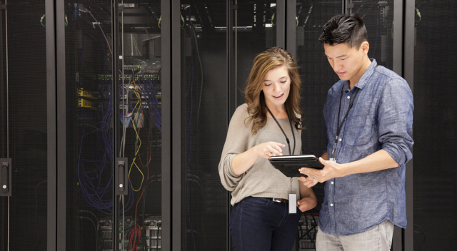 A man and a woman standing in front of a server looking at a tablet.