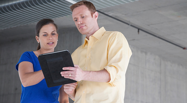 2 people checking tablets