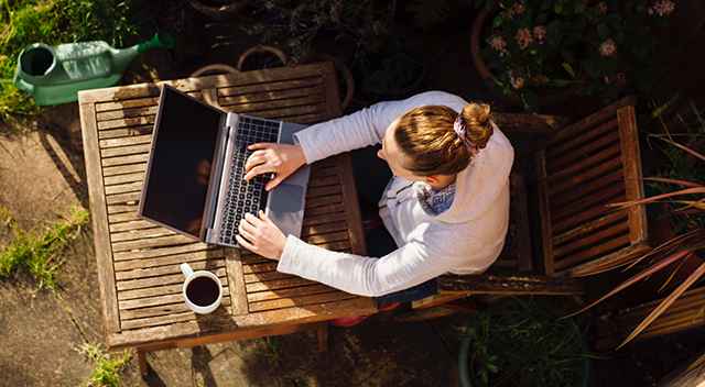 Woman working outside on her laptop.
