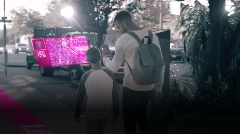 Boy and man walking down the street looking at a mobile phone and a virtual overlay of a map in front of them.