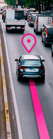 A car driving down the highway with a magenta line trailing behind it and a magenta locator pin hovering above it.