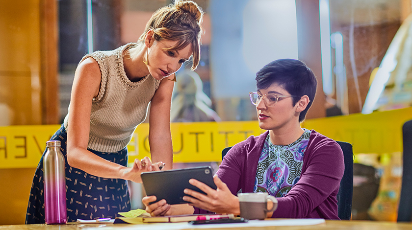 Two women at a desk—one seated and one standing—looking at a tablet.