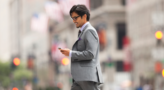 Man outside looking at phone