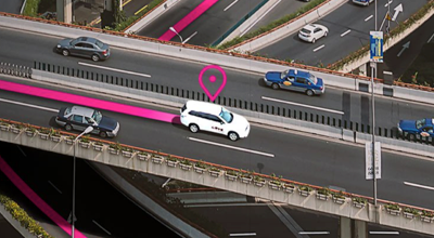 Van driving down the highway with a magenta line following behind it and a magenta locator icon above it.