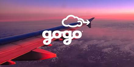 Airplane wing with sunsetting sky, clouds and the Gogo logo.