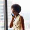 Mujer parada junto a una ventana hablando por celular.