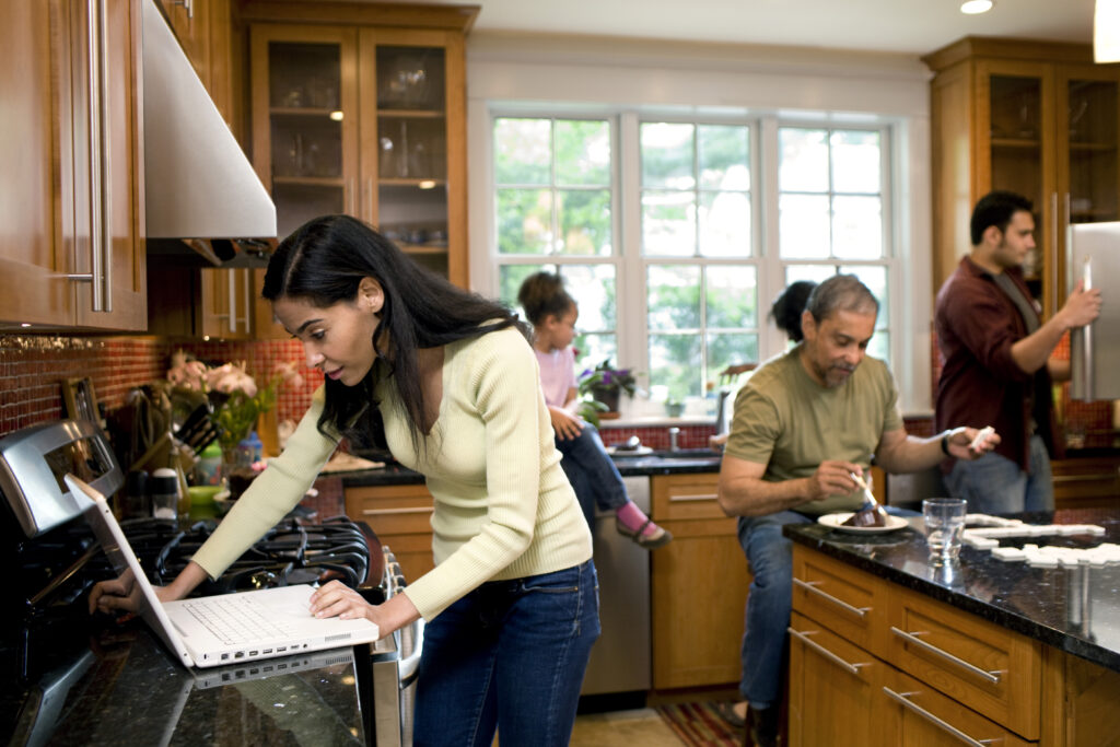 Woman looks at laptop while multigenerational family moves around kitchen in background