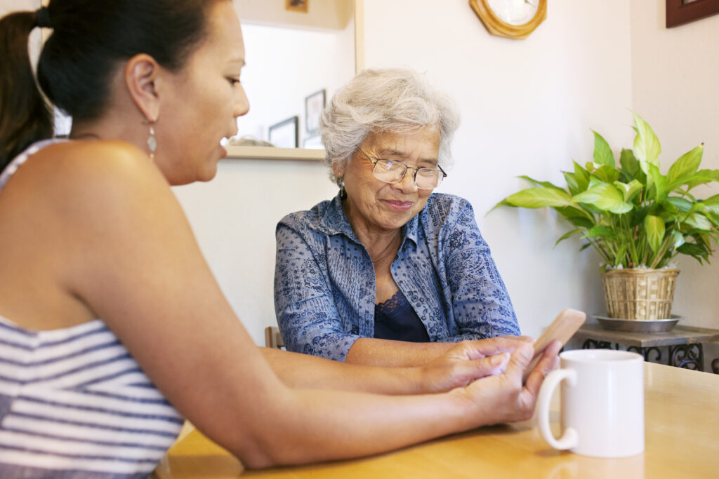 Middle aged woman showing phone to older woman